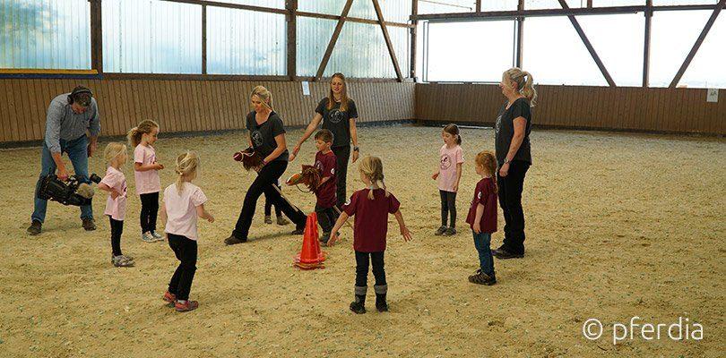Kinder lernen Reiten in einem gemeinsamen Spiel