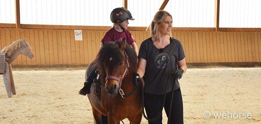 Kolly Holland-Nell führt Pony, darauf sitzt ein Kind.