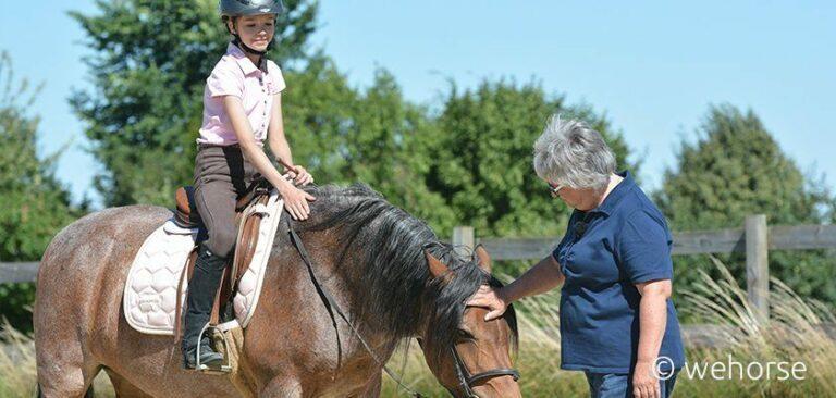 Ausbilderin Sibylle Wiemer neben Pferd und junger Reitschülerin