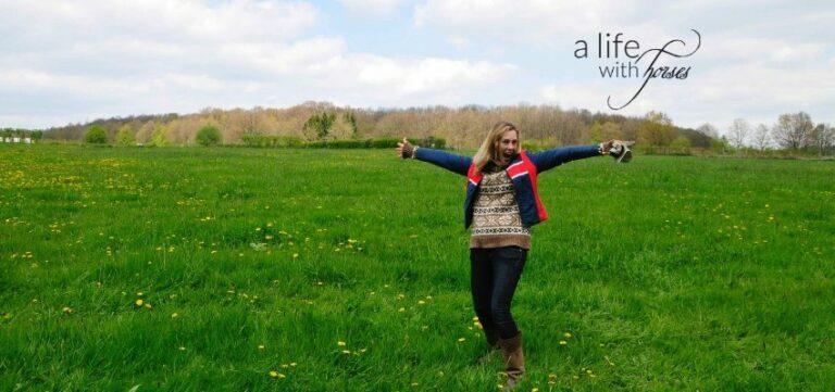 Frau auf großer Weide breitet Arme aus