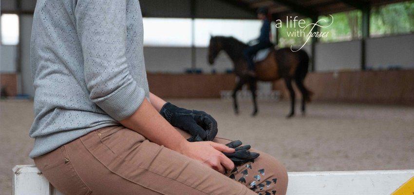 Reiterin im Vordergrund ohne Pferd, Pferd unscharf im Hintergrund